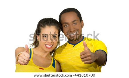 Charming interracial couple wearing yellow football shirts giving thumbs up to camera, white studio background - stock photo
