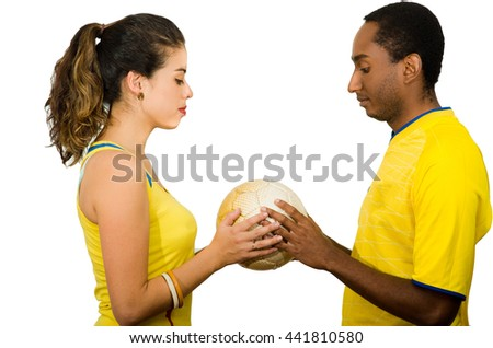 Charming interracial couple wearing yellow football shirts holding ball between each other, profile angle white studio background - stock photo