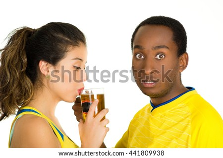 Charming interracial couple wearing yellow football shirts, posing for camera while woman drinks from beer glass and man with surprised facial expression, white studio background - stock photo
