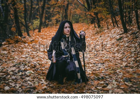 Charming lady with dreadlocks wearing black mantle  with books standing by the old tree in the autumn forest. Fantasy and Halloween image.