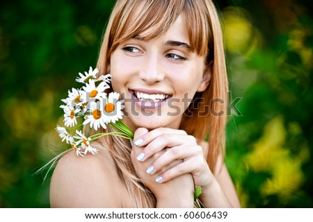 Charming laughing young woman with bouquet of camomiles, on green summer background. - stock photo