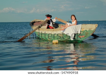 Charming little boy dressed as a pirate and his old lady floating in a boat on a background of blue sea/Theatrical performance of the pirates outdoors - stock photo