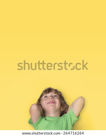 Charming little boy looking up portrait on yellow background    - stock photo