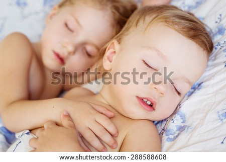 charming little brother and sister asleep embracing  - stock photo