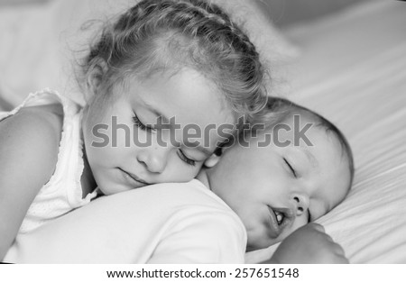 charming little brother and sister asleep embracing ( black and white ) - stock photo