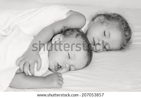 charming little brother and sister asleep embracing on white background  ( black and white )
