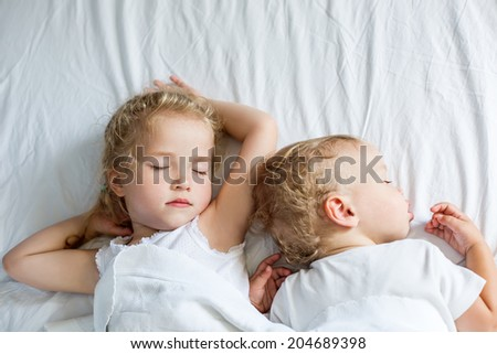 charming little brother and sister asleep  on white background - stock photo