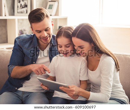 Charming little girl and her beautiful young parents are using a digital tablet and smiling while sitting on sofa at home