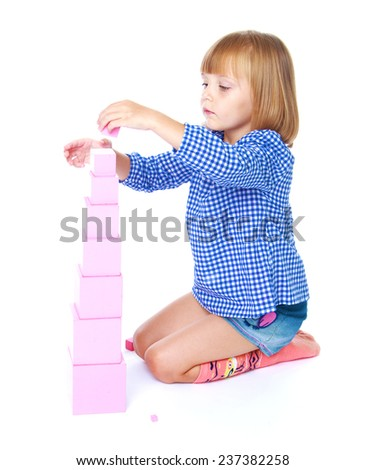 charming little girl collects in the Montessori classroom pyramid isolated on a white horse - stock photo