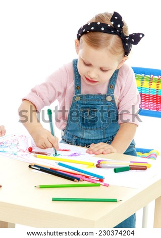 Charming little girl draws with markers while sitting at table.Childhood education development in the Montessori school concept. Isolated on white background. - stock photo
