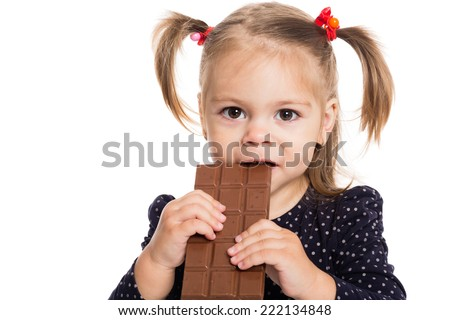 Charming little girl eating chocolate. Two years. - stock photo