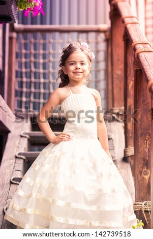 Charming little girl in a beautiful dress in a park outdoor