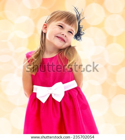 Charming little girl in a pink dress with a white bow. Happiness, winter holidays, new year, and childhood. - stock photo