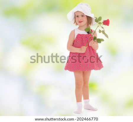 charming little girl in a red sundress and a red rose in his hand.active lifestyle,happiness concept,carefree childhood concept. - stock photo
