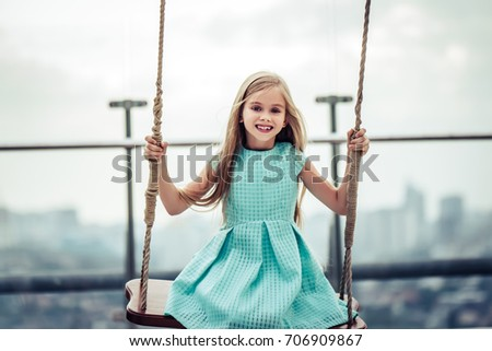 Charming little girl in beautiful dress is having fun on a swing. Smiling and looking at the camera.