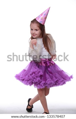 Charming little girl in holiday dress posing for the camera and smiling