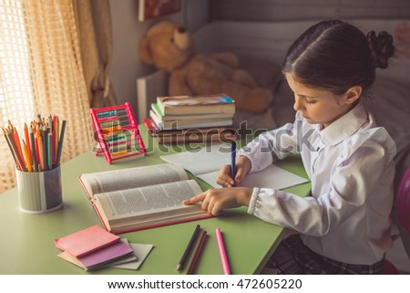 Charming little girl in school uniform is reading and writing while doing homework at the desk at home