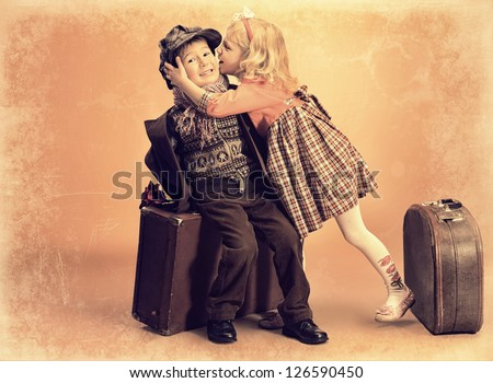 Charming little girl is kissing cute little boy sitting on the old suitcase. Retro style. - stock photo