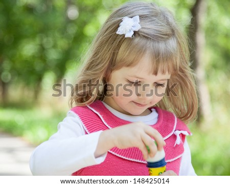 Charming little girl making soap bubbles in a summer park