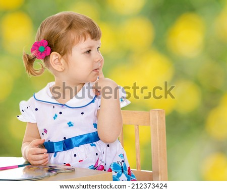 Charming little girl reading a book while sitting at a table in the Montessori classroom.the concept of a happy childhood, education of children, teens - stock photo