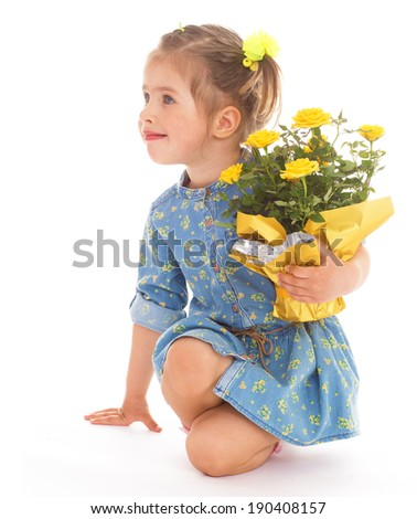 Charming little girl sitting with a bouquet of yellow roses
