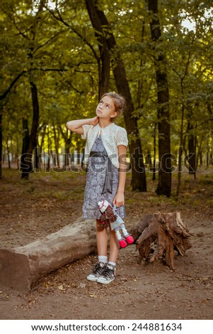 Charming little girl standing near  tree in forest with  doll in hands