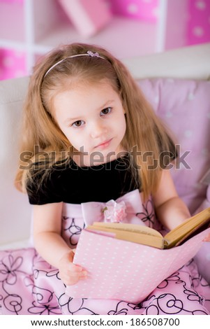Charming little girl wearing beautiful pink dress reading book with her on white sofa in bright pink room - stock photo