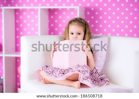 Charming little girl wearing beautiful pink dress reading book with her on white sofa in bright pink room hiding by the book - stock photo