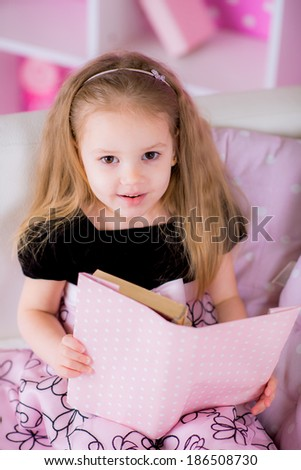 Charming little kid wearing beautiful pink dress reading book with her on white sofa in bright pink room - stock photo