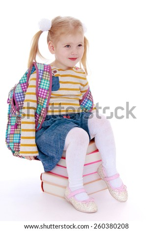 charming little schoolgirl with satchel behind him sitting on a pile of books - isolated on white. - stock photo