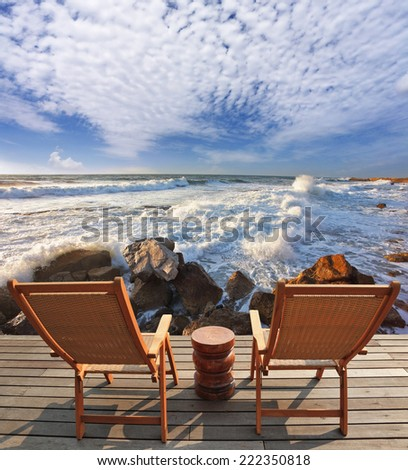 Charming lookout for two. Two convenient comfortable guest sun loungers and a bedside table are worth on a wooden platform. It is well-admired stormy sea surf - stock photo