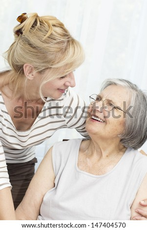 Charming mature daughter hugging her senior mother . - stock photo
