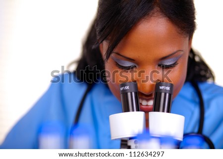 Charming medical nurse female using a microscope at laboratory in blue uniform