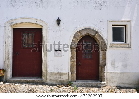 Charming medieval street of the old town Evoramonte in Portugal. White plastered wall, two wooden doors and window