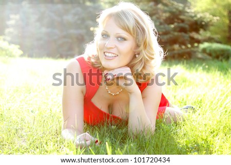 Charming mid adult woman lying on grass and smiling. Summertime