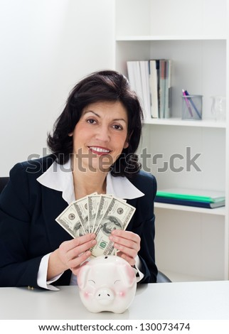 Charming money mature businesswoman sitting at the table, and holding a  cash. - stock photo