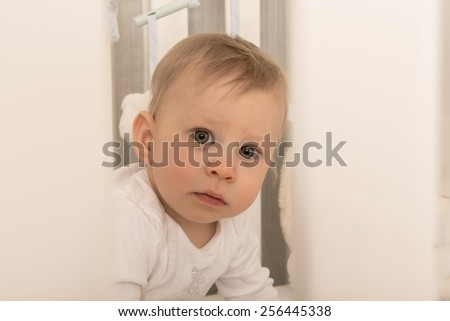 Charming 8 months old baby boy looking curious, sitting in his bed. - stock photo