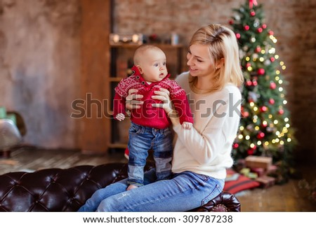 Charming mother blonde in the white sweater looks at his little toddler son in a red sweater and smiling on the background of Christmas trees and garlands in the house - stock photo