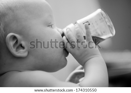 Charming mother feeding her adorable son in the kitchen at home - stock photo