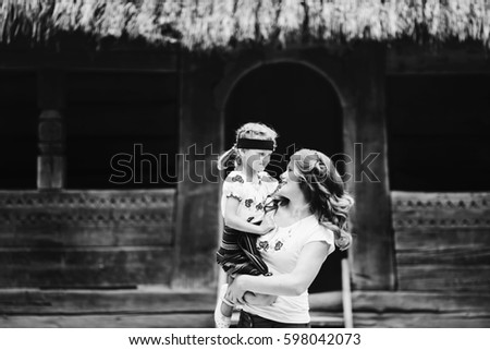 Charming mother holds on her arms little girl in ethnic clothes
