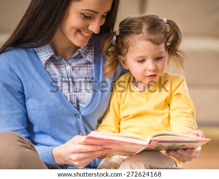 Charming mother is showing images in a book to her cute little daughter at home. - stock photo