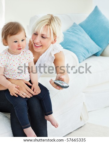 Charming mother playing with her daughter in living room