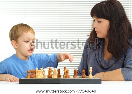 Charming mother with her son sitting playing chess on light background - stock photo