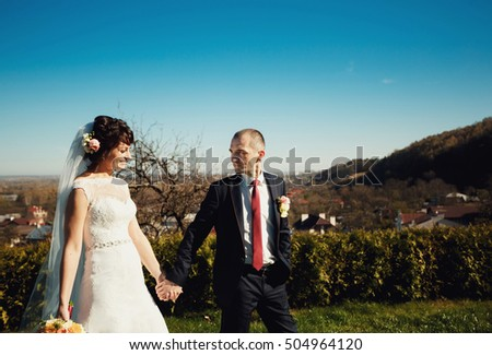 Charming newlyweds walking on the pretty courtyard