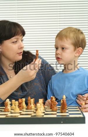 Charming nice mama with her son sitting playing chess on light background - stock photo