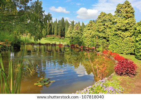 Charming park Sigurta in northern Italy. Picturesque bushes with red flowers at a round pond