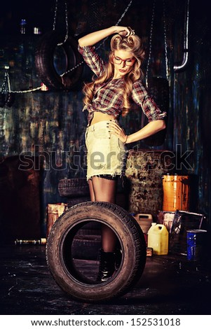 Charming pin-up woman with retro hairstyle and make-up in the old garage. - stock photo