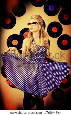 Charming pin-up woman with retro hairstyle and make-up posing with vinyl record. - stock photo