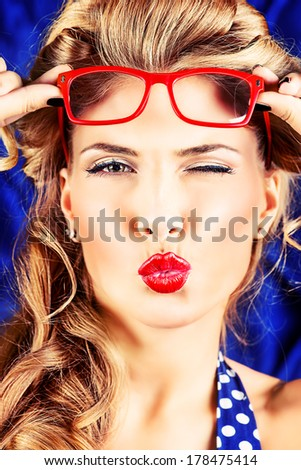 Charming pin-up woman with retro hairstyle and make-up sending a kiss. - stock photo