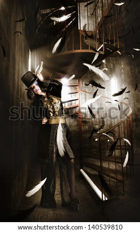 Charming portrait of an elegant fashion girl making a magic wish in top hat, stylish black haircut and jester make up. Medieval castle interior - stock photo